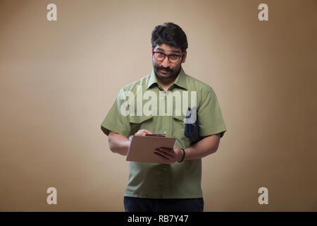 L'homme portant des lunettes à écrire des notes sur un bloc-notes portant un petit sac. Photo Stock