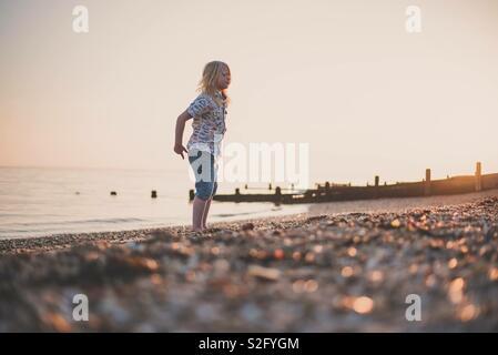 Enfant sur la plage au coucher du soleil Photo Stock