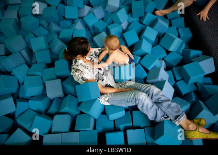 La mère et l'enfant jouer dans une fosse de cubes de mousse bleu. Photo Stock