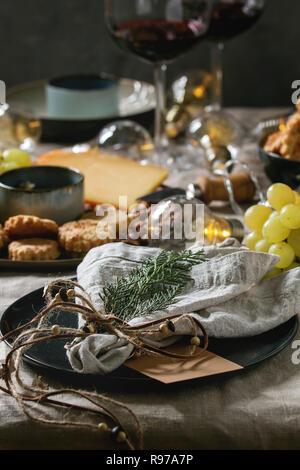 Accueil Noël ou Nouvel an jeu de table de dîner avec vin, assiette de fromage, apéritifs, foudre Garland, décoration de Noël et vide la plaque avec serviette en tissu. Photo Stock