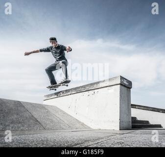 Jeune homme sur le toit de planche à roulettes Photo Stock