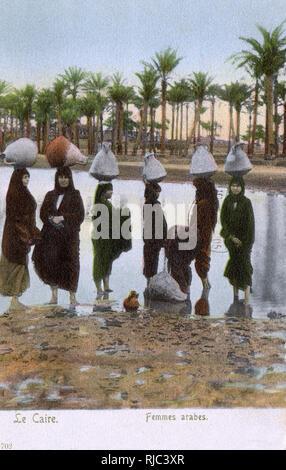 Les femmes arabes transportant de grandes amphores d'eau - Le Caire, Egypte. Photo Stock
