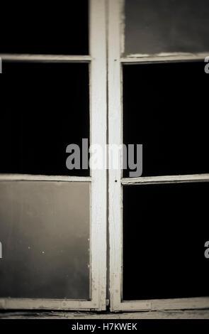 Vieille fenêtre cassée avec verre manquant. Maison abandonnée détail. Photo Stock