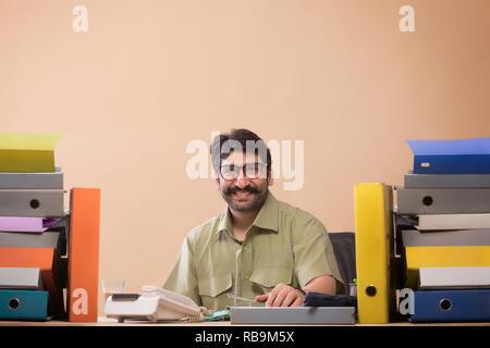 Smiling businessman looking at files assis à son bureau avec un verre de thé à la main. Photo Stock