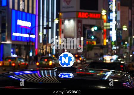 Toit de taxi et de néon enseignes publicitaire dans la nuit dans le quartier de Shinjuku, Tokyo, Japon. Photo Stock
