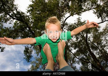 Jeune garçon en équilibre sur les pieds avec les bras Photo Stock