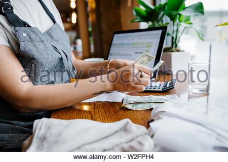 Serveuse en comptant les conseils au comptoir dans restaurant Photo Stock