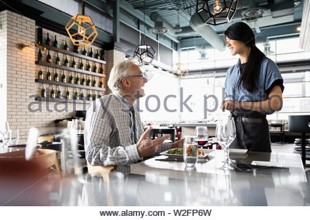 Friendly man waitress in restaurant Photo Stock