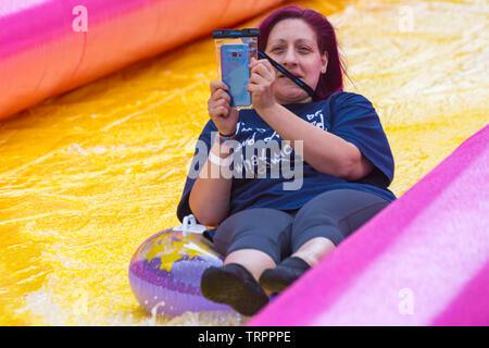Femme sur anneau gonflable s'amusant et en prenant sur les selfies toboggan géant, toboggan, à Bournemouth, Dorset UK en Juin Photo Stock
