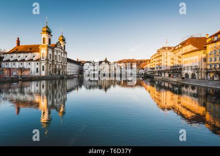 Lucerne, Suisse. Église des Jésuites et le secteur riverain de la rivière Reuss, au lever du soleil Photo Stock