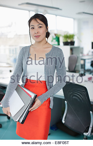 Confident businesswoman holding folders in office Photo Stock