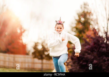 Girl avec unicorn bandeau running in park Photo Stock