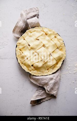 Tarte non cuite avec un large réseau sur le dessus. Arrière-plan de béton, processus de préparation. Photo Stock