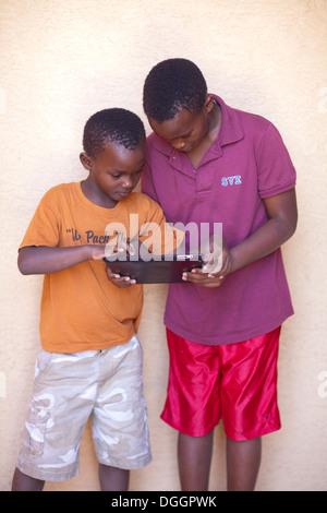 Deux frères du Rwanda découvrez des jeux sur un ipad. Photo Stock
