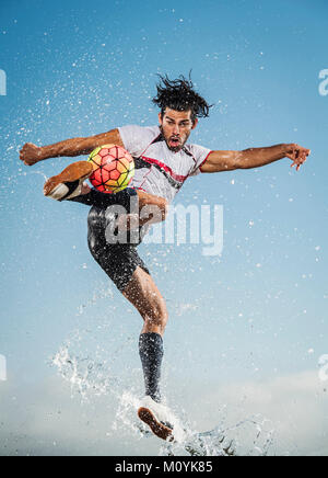 Pulvérisation d'eau sur man kicking soccer ball Photo Stock
