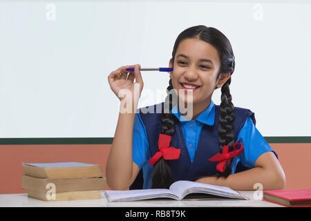 L'école Smiling girl holding pen Photo Stock