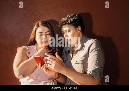 Deux amis à la recherche de téléphone cellulaire. Photo Stock