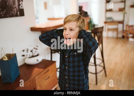 Espiègle, silly boy sticking out tongue et couvrant les oreilles Photo Stock