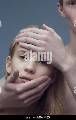 Mains de l'homme de race blanche sur le visage de femme Photo Stock