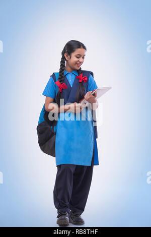 La fille rurale, en uniforme d'holding books et sac Photo Stock