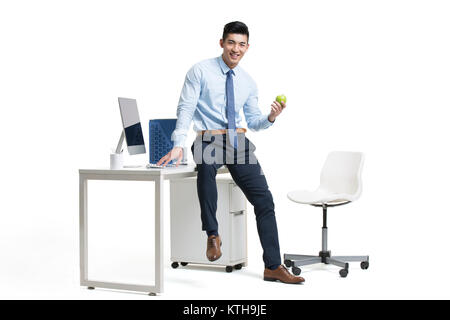 Young businessman holding apple in office Photo Stock