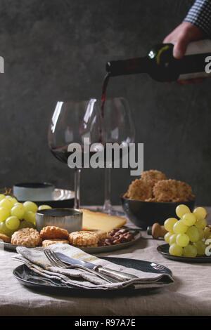 Accueil dîner table set avec vin, assiette de fromage, apéritifs et vide la plaque avec une serviette en tissu. La main de l'homme verse le vin de la bouteille Photo Stock