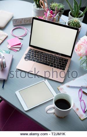 Ordinateur portable rose, café et des fournitures de bureau sur 24 Photo Stock