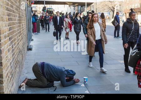 L'Angleterre, Londres, Southwark, London Bridge City, les navetteurs en passant devant Street mendiant Photo Stock