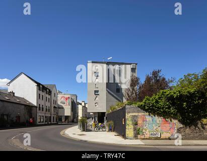 Street view lointain avec cinema's nom gravé dans la façade en béton. Pálás Cinéma, Galway, Irlande. Architecte: dePaor, 2017. Photo Stock