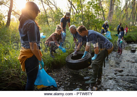Bénévoles, le nettoyage des ordures et des pneus en stream Photo Stock