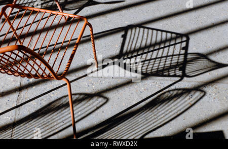 Siège en métal peint des ombres sur un sol en béton gris Photo Stock