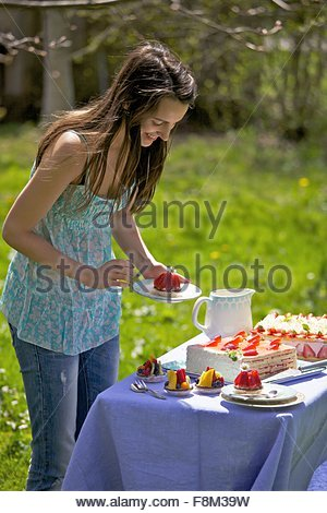 Une jeune femme par un buffet de gâteaux l'extérieur Photo Stock