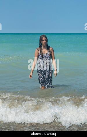 Une jeune fille debout dans un lac dans les vagues Photo Stock