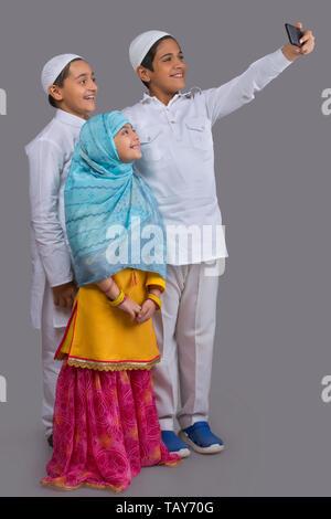 Les jeunes enfants musulmans en tenant ensemble selfies Photo Stock