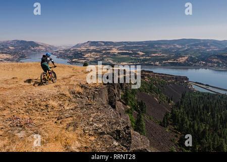 Man mountain biking sur falaise le long de la rivière Columbia, Hood River, Oregon, USA Photo Stock