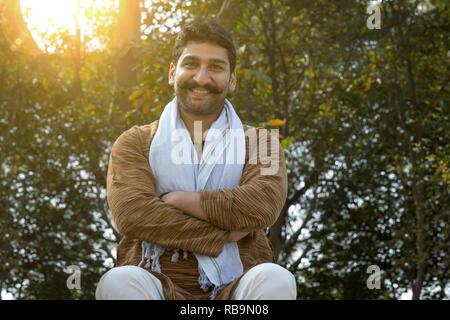 Portrait of a smiling man sitting village avec ses bras croisés avec soleil et arbres en arrière-plan. Photo Stock