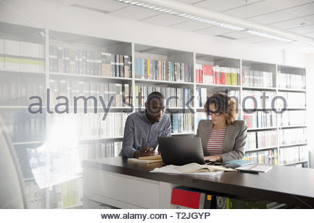 Designers working at laptop in design studio Photo Stock