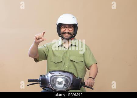 Man wearing helmet assis sur un scooter et geste montrant de la tenue d'un produit avec les doigts. Photo Stock