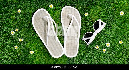 Des sandales et des lunettes de soleil sur un lit d'herbe et de fleurs, pour illustrer le printemps, l'été Photo Stock