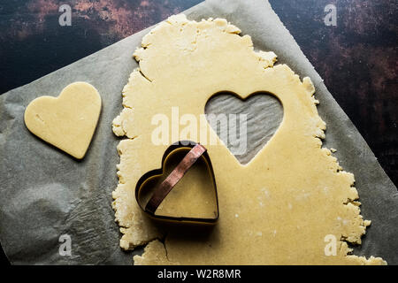 High angle close up of heart-shaped cookies coupé de la pâte. Photo Stock