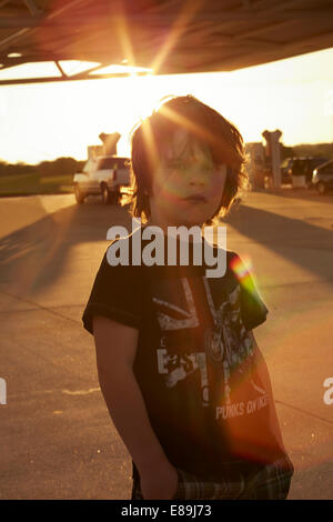 Boy standing at gas station au coucher du soleil Photo Stock