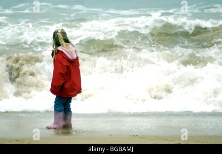 Jeune fille à la recherche à une grosse vague sur la plage en hiver. Photo Stock