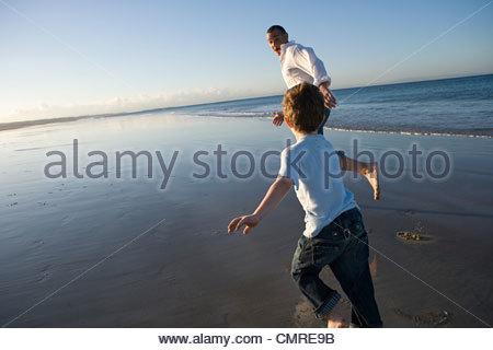 Père et fils d'exécution par la mer Photo Stock