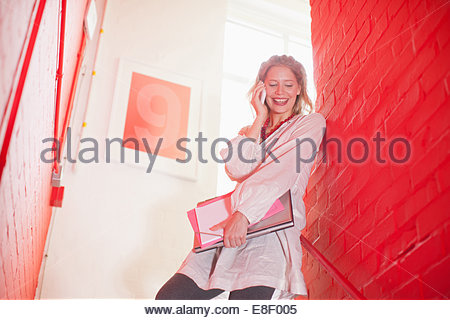 Smiling businesswoman holding folders et talking on cell phone in d'escalier Photo Stock