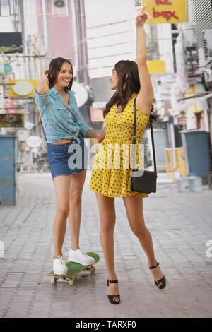 Femme marche sur rue avec son amie sur planche Photo Stock