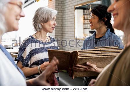 Serveuse montrant menu pour les femmes âgées amis dans restaurant Photo Stock