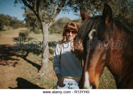 Une femme debout à l'extérieur avec un cheval Photo Stock