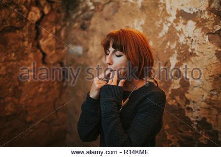Portrait d'une jeune femme debout contre un mur de siffler Photo Stock