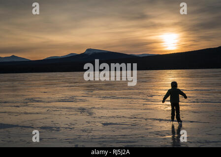 Enfant patinant sur un lac gelé Photo Stock
