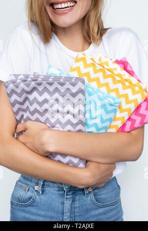 Femme tenant des tissus colorés zigzag Photo Stock